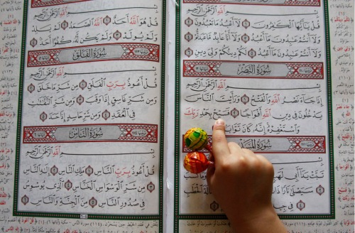 boy holds candy as he reads quran
