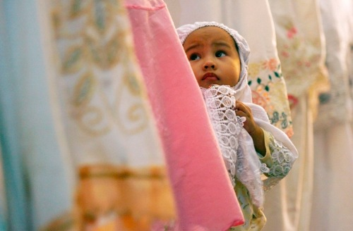 child stands among worshippers