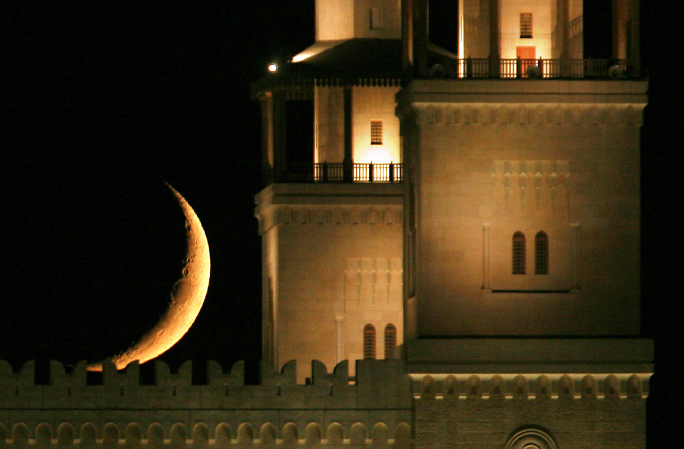 crescent moon behind mosque