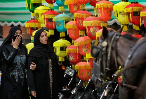 egyptian women walk past paper lantern