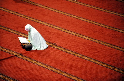 muslim woman reads quran at istiqlal mosque
